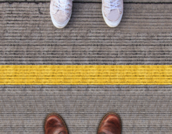 Two feet standing on each side of a yellow line