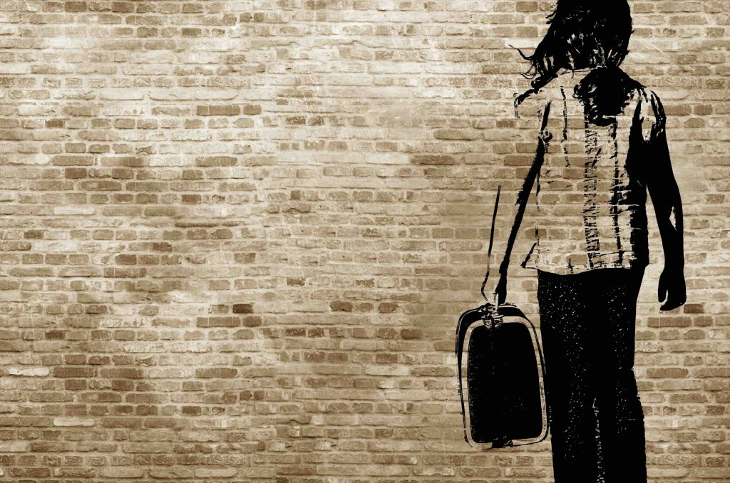 shadow on a brickwall showing a girl walking with her suitcase