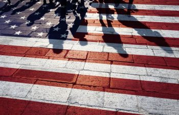 Shadow of pedestrians crossing, American flag painted on the ground