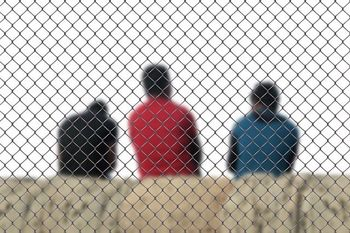 Three man are separated in front of fence, deportation